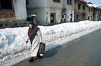 Bosnia and Herzegowina. Republika Serpska. Srebrenica. A muslim woman walks on the concrete road near a row of private houses destroyed by the war. Winter season. © 2005 Didier Ruef