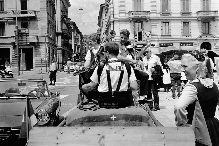 Switzerland. Canton Ticino. Lugano. Federal Choir Festival in Costume. The beauty and tradition of costumes from all regions of Switzerland. A group of musicians seat on a charriot and play accordion, violin and bass. A blanked from the swiss army with a white cross. A man in a convertible car. A policeman and a private security guard are taking care of traffic on the road. 12.06.2016 © 2016 Didier Ruef