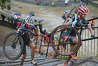 Jolanda Neff (right) of Switzerland carries her bicycle Wednesday, Oct. 13, 2021, in the Union Cycliste Internationale Cyclo-cross World Cup at Centennial Park in Fayetteville. The city was one of 16 sites around the globe to hold a world cup event this year for Union Cycliste Internationale, known as International Cycling Union in the United States. Fayetteville will host the UCI World Championships at Centennial Park Jan. 28-30. Visit nwaonline.com/211014Daily/ for today's photo gallery.<br /> (NWA Democrat-Gazette/Andy Shupe)