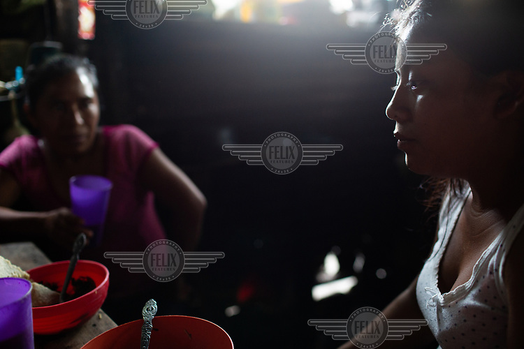 Carmen Garcia (right), 21, and her mother and war survivor Eva Garcia, 39, sit in their kitchen after dinner, at their home in the 15 de Octubre La Trinidad community. Despite fears of the constant activity by the Fuego Volcano, Eva, her daughter and granddaughter, left the Single-Family Temporary Shelters (ATUs) due to the COVID-19 pandemic and returned to La Trinidad. She states: ''Listen!'' (as Fuego Volcano erupts). ''But what can we do? Here at least we have chipilin, and other herbs to eat. But we're all afraid to be back.''