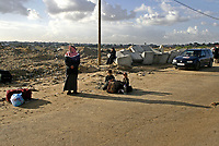 """Palestinian families wait with their luggage to cross the Erez checkpoint from the northern Gaza Strip, 02 December 2007, into Israel on their way to Egypt. Israel today allowed more than 250 Palestinians from the Hamas-run Gaza Strip to cross into Egypt via Israeli territory for the first time in months, witnesses and officials said. . """"photo by Fady Adwan"""""""