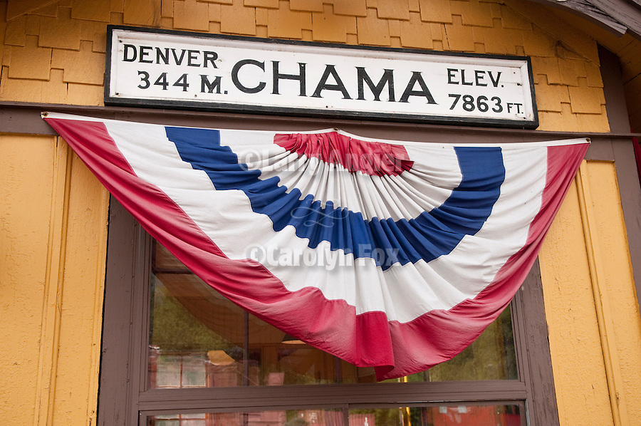 Cumbres & Toltec Scenic Railroad yards at Chama, New Mex...Red, white, blue bunting at the depot: Denver 344 miles, Elevation 7863 ft.