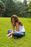 Woman sitting in open field