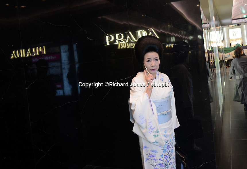 A Japanese shopper wears a Kimono and talks on her mobile phone in front of Prada in the up-market shopping district,  Ginza, Tokyo, Japan.<br /> April-2014