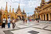 Myanmar, Burma.  Shwedagon Pagoda, Yangon, Rangoon.  Visitors Pass Many Shrines as they Circumambulate the Walkway around the Base of the Stupa.  Two men and woman on left wear the traditional longyi, a wrap-around sarong.