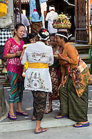 Bali, Indonesia.  Women and Child in Conversation at the Entrance to a Temple.