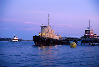 Tugboats at twilight in a shipping channel.