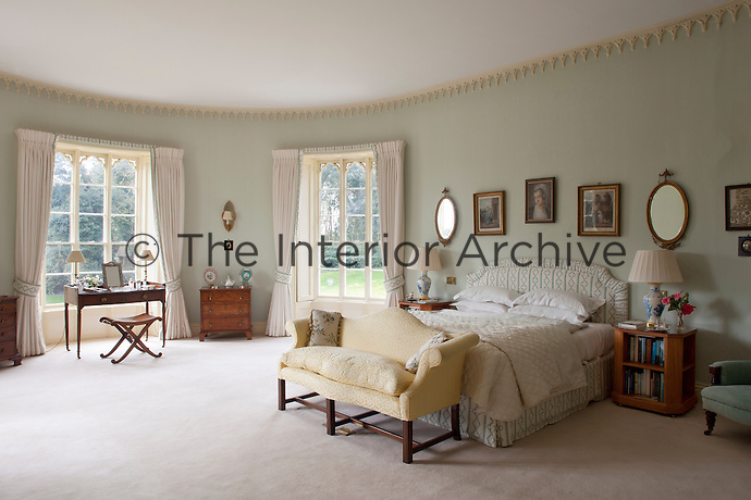 A spacious, curved bedroom with a delicate Gothic plasterwork cornice