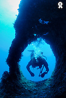 Scuba diver with bubbles swimming through hole in rock (Licence this image exclusively with Getty: http://www.gettyimages.com/detail/sb10065474ej-001 )