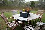 Apple laptop computer sits on garden table at house on Martha's Vineyard