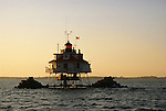 The last light keeper on Chesapeake Bay lowers the flag on Thomas Point Lighthouse near Annapolis in the 1980's.   The lighthouse was automated so thereafter.