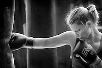 Female boxer hitting the heavy bag.