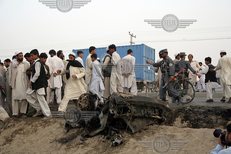 Police chase away looters and onlookers from what remains of a car used in a suicide bomb attack that killed a British soldier.
