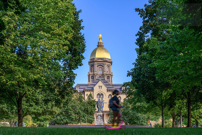 September 15, 2021; Student on a scooter rides past the Main Building, fall 2021 (Photo by Matt Cashore/University of Notre Dame)