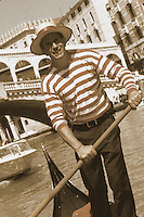 Gondolier navigating a gondola in Venice, Italy