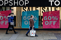 "Last minute Christmas shoppers walk past a ""60% OFF"" sign outside Topshop store in Oxford Street, Swansea, Wales, UK. Monday 24 December 2018"