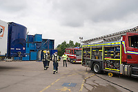 Firefighters in breathing apparatus preparing to enter a factory unit which has been set alight by arsonists. Warwickshire UK. This image may only be used to portray the subject in a positive manner..©shoutpictures.com .john@shoutpictures.com