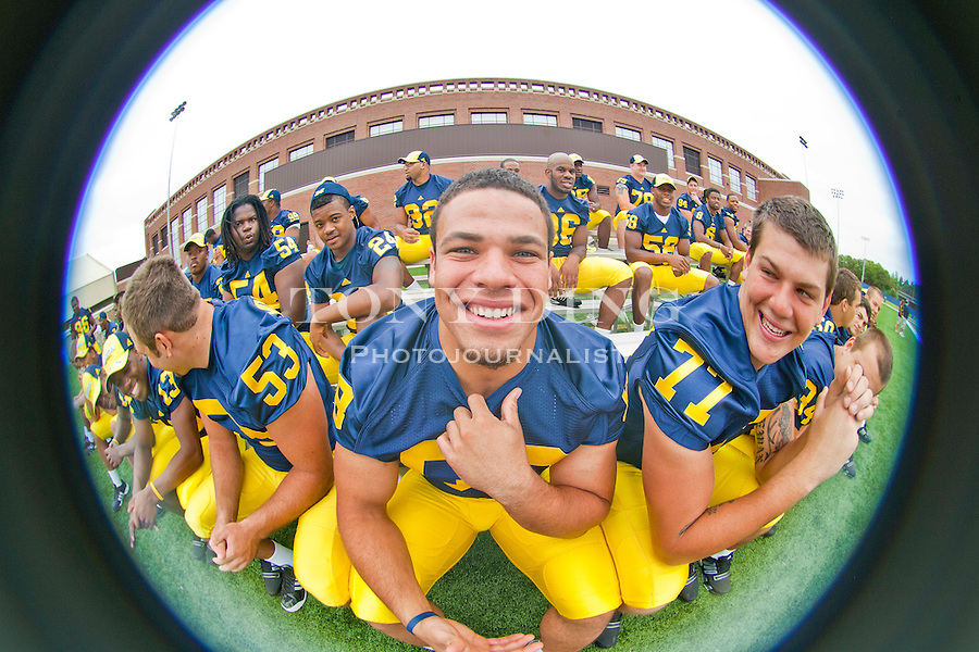 Michigan defensive tackle Mike Martin, center, poses for a picture, at the annual NCAA college football media day, Sunday, Aug. 22, 2010, in Ann Arbor, Mich. (AP Photo/Tony Ding)