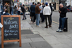 """Super Saturday, bars and pubs open with restrictions in place, social distancing, table service, limited numbers of drinkers in the bar. The Portobello Road Gin Bar """"Welcome Back"""" sign, """"We've Missed You Open 10am- 1am"""" 2020s London 4th July 2020.  2020s UK"""