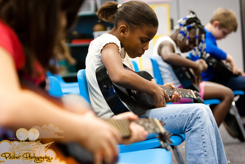 (left to right) Dayla Ware, Marquia Hamilton, A'mya Adams, and Ed Woodring learn guitar on Thursday, December 17, 2009, at Pinewood Elementary School in Mims, Florida. Darci Halloran, a music teacher, was teaching a 2nd grade class of students how to play guitars. Halloran was awarded a grant to purchase guitars for her music students. (Chad Pilster, http://www.PilsterPhotography.com)