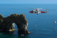BNPS.co.uk (01202 558833)<br /> Pic: Graham Hunt/BNPS<br /> <br /> The coastguard helicopter lands on the beach at Durdle Door in Dorset to deal with a medical emergency on an afternoon of scorching hot sunshine and clear blue skies.<br /> <br /> The coastguard helicopter takes off from the beach past the iconic sea arch.