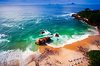 Praya do Vidigal aerial view, with white umbrellas, beautiful rocks, and ocean wave shapes on the sand, near Ipanema Beach in Rio de Janeiro, Brazil