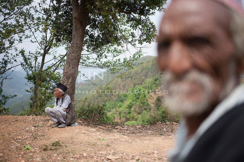 A survivor of Nepal earthquake sits under a tree near at Jalkeli village, outskirts of Kathmandu, Nepal. May 1, 2015