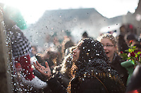 A young girl is covered by confetti along a bridge over the river Reine, by participants in the first day of Fasnacht, the Carnival of Basel, Switzerland. Feb. 23, 2015.