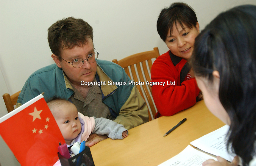A Canadian couple and their newly adopted daughter are questioned by Government officials during the final stages of the adoption procedure. The family were part of a group of Canadian nationals go through the adoption procedure in Changsha, Hunan, China.