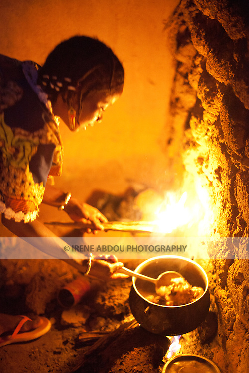 """A woman in Djibo, Burkina Faso cooks millet """"pot,"""" similar to the Italian polenta.  Without a stove or electricity, women throughout West Africa cook outside on open fires."""