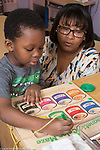 Education Preschool 3 year olds female teacher observing as boy does magnet color sorting puzzle