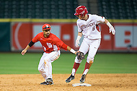 Eric Cole (8) of the Arkansas Razorbacks beats the tag from Houston Cougars shortstop Jose Reyes (12) at Minute Maid Park on February 27, 2016 in Houston, Texas.  The Razorbacks defeated the Cougars 12-3.  (Brian Westerholt/Four Seam Images)