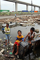 Children play in a flooded community in northern Jakarta.<br />