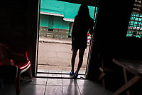A Salvadoran sex worker, waiting for clients, stands in the door of a street sex bar in San Salvador, El Salvador, 19 December 2013. Although prostitution is not legal in El Salvador, dozens of street sex workers, wearing provocative miniskirts, hang out in the dirty streets close to the capital's historic center. Sex workers of all ages are seen on the streets but a significant part of them are single mothers abandoned by their male partners. Due to the absence of state social programs, they often seek solutions to their economic problems in sex work. The environment of street sex business is strongly competitive and dangerous, closely tied to the criminal networks (street gangs) that demand extortion payments. Therefore, sex workers employ any tool at their disposal to struggle hard, either with their fellow workers, with violent clients or with gang members who operate in the harsh world of street prostitution.