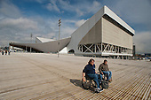 Two men in wheelchairs pass by the Aquatics Centre, designed by architect Zaha Hadid, in the Olympic Park, London.