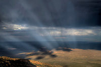 A passing thunderstorm produces distinct sunbeams over Marble Canyon, Arizona