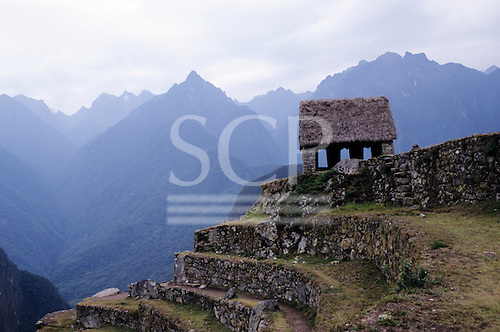 Machu Picchu, Peru. Terraces and an Inca shelter with modern thatch.