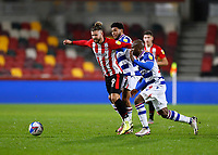 19th December 2020; Brentford Community Stadium, London, England; English Football League Championship Football, Brentford FC versus Reading; Emiliano Marcondes of Brentford is challenged by Andy Rinomhota and Sone Aluko of Reading