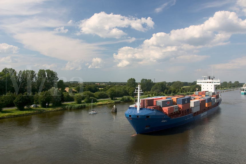 Cargo ship and sailboat along the Kiel Canal in Germany.