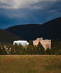 the setting sun lights up buildings in downtown missoula, montana