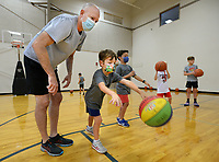 Volunteer coach Matt Bishop (left) shows camper Buckley Newell, 6, how to make a bounce pass Tuesday, Aug. 3, 2021, during basketball skills camp at St. Joseph Catholic School in Fayetteville. The camp is hosting about 100 students from kindergarten to eighth grade for a week of basketball fundamentals. Visit nwaonline.com/210803Daily/ for today's photo gallery.<br /> (NWA Democrat-Gazette/Andy Shupe)