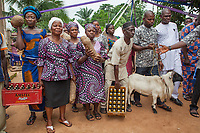 Nigeria. Enugu State. Agbani. Igbo funeral ceremony of Mrs Ann Mary Azuka Nbubuisi Anike who passed away at 72 years old. The burial takes place in the family home's garden. Guests invited to the funeral bring offerings as gifts to the family of the dead woman. A crate of Amstel beers, Yam vegetable roots, another crate of beers, a goat. The women wear a head tie which is a women's cloth head scarf. The head tie is used as an ornamental head covering or fashion accessory. Its use or meaning can vary depending on the country and/or religion of those who wear it. The head tie is called gele in Nigeria. 11.07.19 © 2019 Didier Ruef