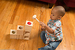 21 month old toddler boy playing with pound a ball wooden maze toy