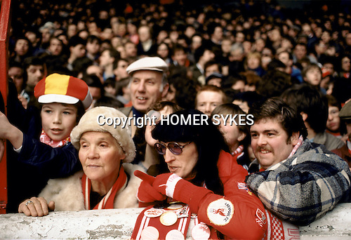 Family outing at the Kop stands,  Anfield football stadium. Liverpool football fans 1980s wearing red. Supporters in the Kop - single tier terraces and stands watching match.<br /> Red was their colour.
