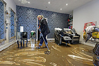 Pictured: Laura Court clears up mud from the floor of Lougos hair dressers. Monday 17 February 2020<br /> Re: Cleanup after storm Dennis in Oxford Street, Nantgarw, Wales, UK.
