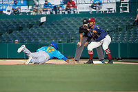 Frisco RoughRiders first baseman Andretty Cordeo (4) waits for a pickoff attempt throw as Buddy Reed (12) dives back to the bag with umpire Darius Ghani looking on during a Texas League game against the Amarillo Sod Poodles on May 19, 2019 at Dr Pepper Ballpark in Frisco, Texas.  (Mike Augustin/Four Seam Images)