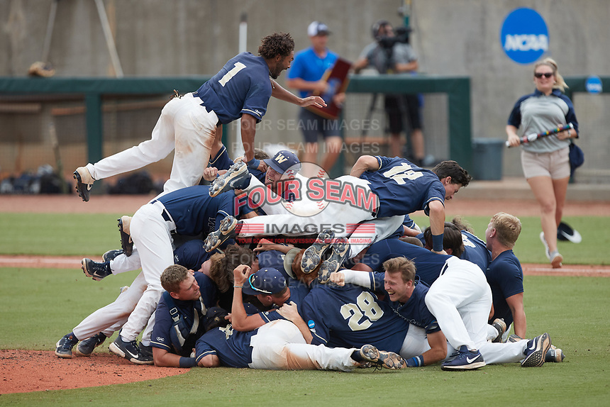 Wingate Bulldogs center fielder Justin Guy (1) leaps on top of the pile of his teammates following the final out against the Central Missouri Mules during the 2021 DII Baseball National Championship at Coleman Field at the USA Baseball National Training Complex on June 12, 2021 in Cary, North Carolina. The Bulldogs defeated the Mules 5-3. (Brian Westerholt/Four Seam Images)