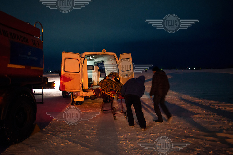 A patient is loaded into an ambulance at the airport after being transported by helicopter from Kellog, a remote Siberian community.