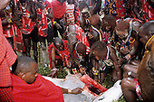 Lolgorian, Kenya. Eunoto coming of age ceremony; moran Maasai warrior drinking the blood of a scrificed bull.