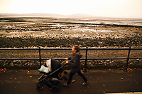 Pictured: A woman walks with a pushchair at the seaside village of Mumbles near Swansea, UK. Monday 16 October 2017<br />